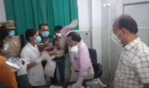 En indisk sykepleier klappet til en lege etter en angivelig uenighet om en dødsattest for en covid-19-pasient på et sykehus i Rampur. Bildet viser den indiske legen idet han reiser seg opp for å gjengjelde slaget.