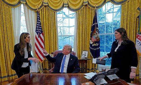 USAs president Donald Trump avbildet sammen med kommunikasjonssjef Hope Hicks (til venstre) og pressesjef i Det hvite hus, Sarah Huckabee, (til høyre) i Det ovale kontor i januar måned.