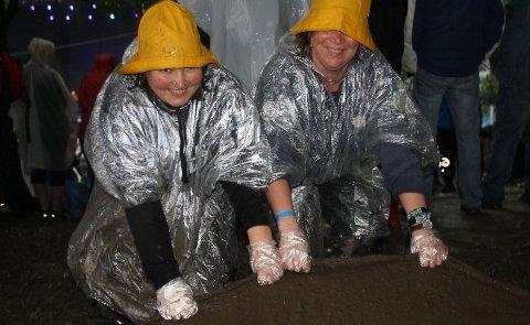 Mette Furu fra Ekeberg og Guri Meringdal fra Røa er begge frivillige under Norwegian Wood, i Trivsel og Miljø-gruppa. Her forsøker de å sikre en av gangveiene på festivalområdet.