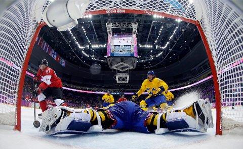 Canadas stjerne Sidney Crosby scorer mot Sveriges Henrik Lundqvist i OL i Sotsji i 2014. Foto: Julio Cortez / NTB / AP.