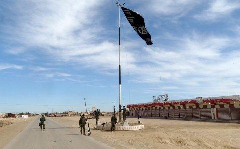 Irakiske sikkerhetsstyrker fjerner et IS-flagg vest for byen Ramadi i begynnelsen av mars.