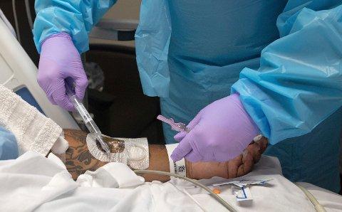HARDT PRESSET: En sykepleier gir legemidler til en koronapasient ved Our Lady of the Lake medisinske senter i Baton Rouge. Byen ligger i Louisiana, en av delstatene der presset på sykehusene er høyere nå enn under den forrige koronatoppen i vinter.