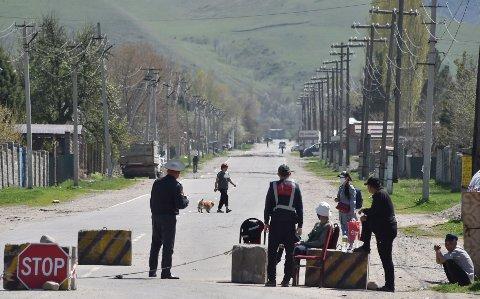 Kirgisisk politi avbildet ved en kontrollpost. Myndighetene i Kirgisistan blir kritisert av Amnesty for brudd på menneskerettigheter, deriblant for å ha stengt samtlige beboere inne i en boligblokk ved å sveise igjen dørene.