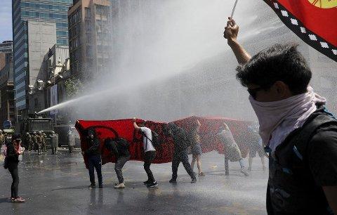 KREVER REFORMER: Politiet bruke vannkanoner mot demonstranter i hovedstaden Santiago i Chile. Protestene mot president Sebastián Piñera fortsetter til tross for at presidenten har lovet sosiale reformer.