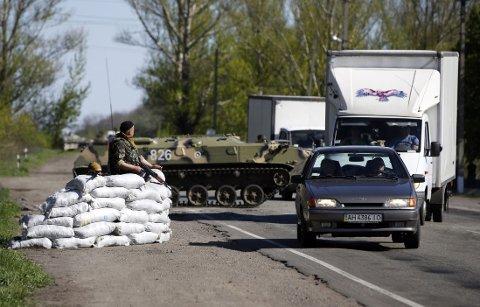 Styrker fra det ukrainske militæret sjekker biler ved et kontrollpunkt øst for Slavjansk torsdag.