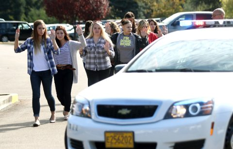 Studenter og ansatte blir evakuert fra Umpqua Community College i Roseburg i Oregon, der en skoleskyting fant sted torsdag.
