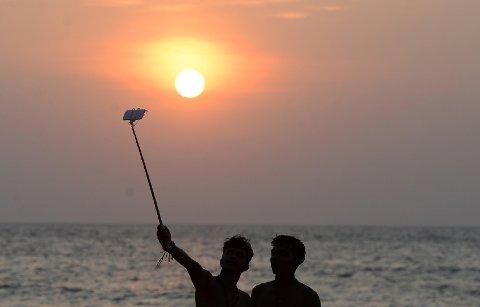 Arkivbilde av to personer som tar en selfie på en strand. Myndighetene i den indiske delstaten Goa har innført 24 selfie-frie soner etter flere selfie-dødsfall den siste tiden.