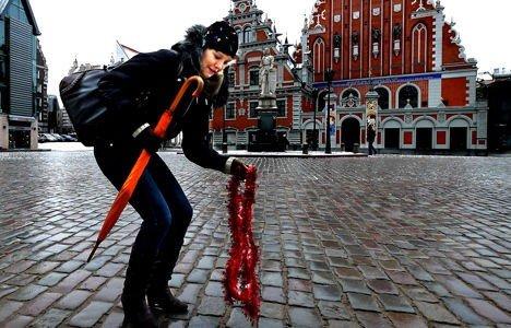 JULEPYNT: Student Leontine Pavlovska plukker opp julepynt fra forrige kvelds festligheter utenfor Svarthodehuset. Her pyntet noen fulle ungdommer verdens første glitrende juletre for 499 år siden.