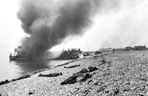 LIK: Ødelagte landingsfartøy med døde allierte soldater i forgrunnen. En tysk bunkers kan sees oppe i høyre hjørne.