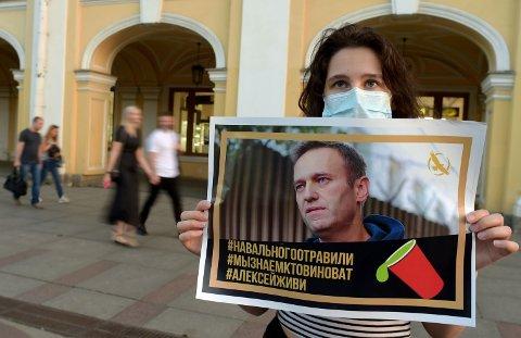 En kvinne med en plakat til støtte for Aleksej Navalnyj i St. Petersburg torsdag.