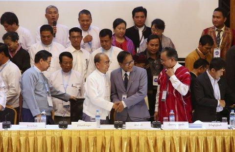 Myanmars president Thein Sein (i hvit jakke) og Naing Han Tha (grå jakke), leder for koordineringsgruppen for våpenhvilen gir hverandre et håndtrykk etter at den nasjonale planen for våpenhvile er signert i Myanmars fredssenter i Yangon trisdag. Avtalen gkal gjøre slutt på en konflikt som har vært i 65 år. Foto: Reuters/NTB scanpix