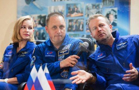 Skuespilleren Julia Peresild (til venstre), regissøren Klim Sjipenko (til høyre) og kosmonaut Anton Sjkaplerov under en pressekonferanse mandag. Tirsdag skal de tre reise til Den internasjonale romstasjonen, der det skal spilles inn scener til en film. Foto: Roskosmos / AP / NTB