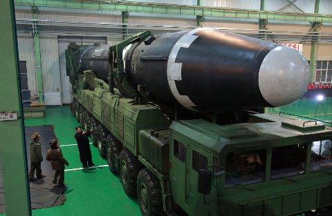 Nord-Koreas leder avbildet ved siden av landets nye interkontinentale ballistiske missil (Hwasong-15).