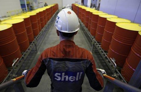Mandag steg oljeprisen rekordraskt som en reaksjon på bortfallet av 5 prosent av den daglige globale produksjonen. Illustrasjonsfoto: En ansatt i Royal Dutch Shell står foran en rekke oljetønner på selskapets fabrikk i Torzhok i Russland.