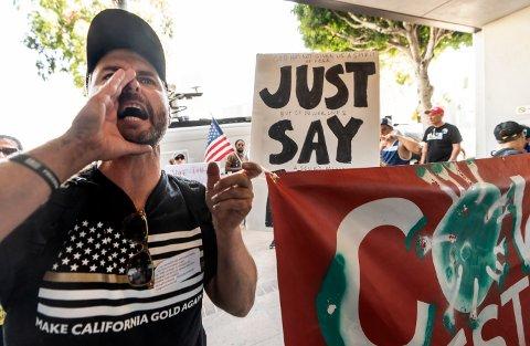 Demonstranter som er imot vaksiner, protesterer utenfor lokalene til skolestyret i Los Angeles som vedtok påbud om vaksinering for alle skoleelever over tolv år. Foto: Damian Dovarganes / AP / NTB