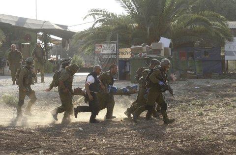 ANGREP: Israelske soldater bærer vekk en såret etter et bombeangrep fra Gazastripen 28. juli. Palestinere hadde sneket seg inn i en palestinsk by og gikk til angrepå mandag.