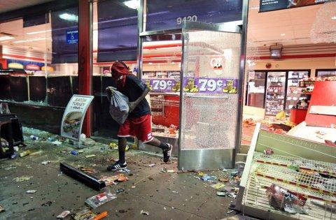 OPPTØYER: En mann løper ut av en butikk etter å ha forsynt seg av vareutvalget. Opptøyene i Ferguson, en forstad til den amerikanske byen St. Louis, startet søndag etter at 18 år gamle Michael brown ble skutt og drept av politiet.