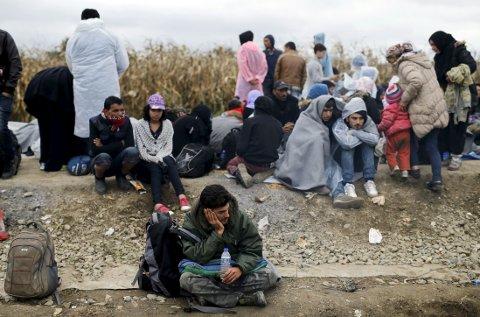 En gruppe flyktninger venter på å få krysse grensen fra Serbia til Kroatia nær landsbyen Strosinci lørdag. I løpet av dagen krysset nesten 10.000 Kroatias grenser.