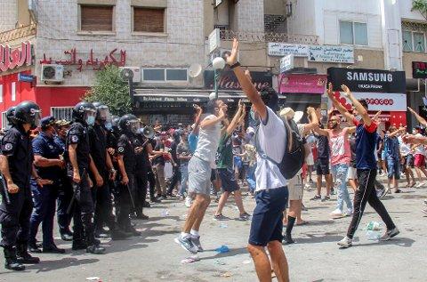 Flere hundre demonstranter samlet seg i Tunisias hovedstad Tunis med krav om at regjeringen måtte gå og parlamentet oppløses. Senere søndag kunngjorde landets president at statsministeren får sparken og at parlamentet suspenderes. Foto: Hassene Dridi / AP / NTB