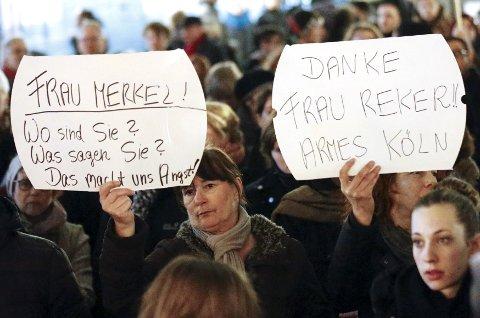 Kvinner holder opp plakater rettet mot statsminister Angela Merkel i forbindelse med en demonstrasjon i etterkant av overgrepene i Köln på nyttårsaften.