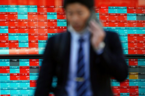 En mann går forbi en skjerm som viser kursene på Nikkei 22-indeksen i Tokyo. Foto: AP / NTB scanpix