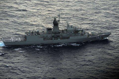 Det australske marinefartøyet HMAS Perth plukker opp en rød gjenstand fra Indiahavet søndag 13. april for å sjekke om den kan stamme fra det savnede flyet til Malaysia Airlines.