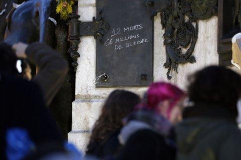 """HELE NASJONEN: Ordene """"Tolv døde, 66 millioner skadet"""" er skrevet på tavlen på en statue på Place de Republique torsdag, som en påminnelse om at terroranslaget angår hele nasjonen."""