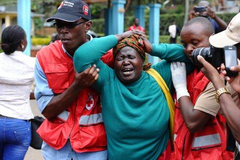 FORTVILET: Hjelpearbeidere fra Røde Kors støtter en kvinne som akkurat har vært og identifisert en død slektning etter torsdagens skolemassakre Kenya.