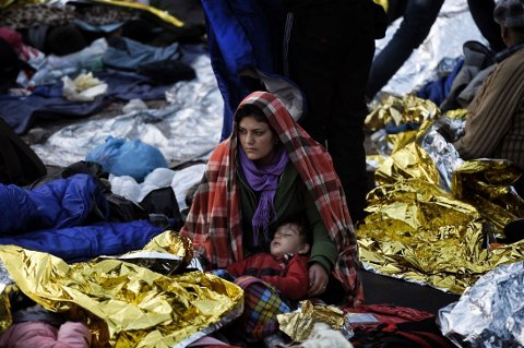 KOM OVER EGEERHAVET: En mor og hennes barn fotografert på Lesbos mandag der de kom i land etter å ha krysset Egeerhavet fra Tyrkia. Europa står midt oppe i den verste flyktningekrisen siden 2. verdenskrig. Hovedbølgen av flyktninger kommer fra borgerkrigsrammede Syria.
