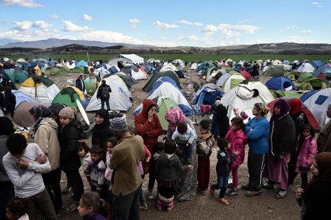 VENTER VED GRENSEN: Folk i matkø nær landsbyen Idomeni ved den gresk-makedonske grensen fredag. Tusenvis av migranter og flyktninger er strandet her. Samtidig pågår de diplomatiske anstrengelsene for å få kontroll på asyltilstrømmingen.