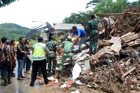 Et redningsteam og frivillige gjør en innsats i et område i Sumedang som er rammet av flom og skred.