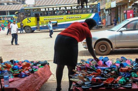 En kvinne selger plastsko på et gatemarked i Kampala i Uganda. Klimaendringer forverrer eksisterende ulikheter mellom kjønnene, viser ny rapport fra Care. Foto: AP / NTB scanpix