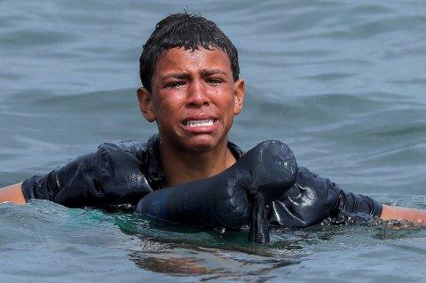 SVØMMER OVER: En ung gutt gråter mens han prøver å svømme i land ved hjelp av en bøye og plastflasker på grensen mellom Marokko og enklaven Ceuta.