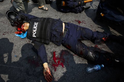SKADET POLITIMANN: Flere er drept og enda flere er skadd i blodige sammenstøt i Bangkok tirsdag. Her ligger en hardt skadd politimann på bakken mens han får legehjelp.
