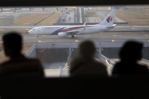 Passasjerer ser ut på et fly fra Malaysian Airlines på flyplassen i Kuala Lumpur. Hva som har skjedd med flight MH370 og de 239 passasjerene som var om bord er fortsatt et mysterium.