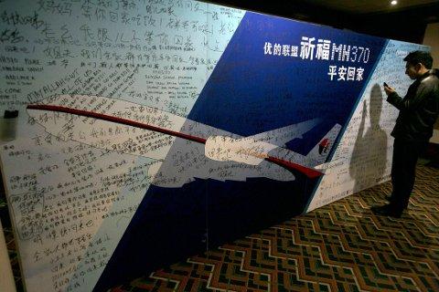 BER FOR MH370: På en tavle i Kinas hovedstad Beijing skriver folk ned lykkeønskninger til berørte etter at Malaysian Airlines flygning MH370 forsvant sporløst.