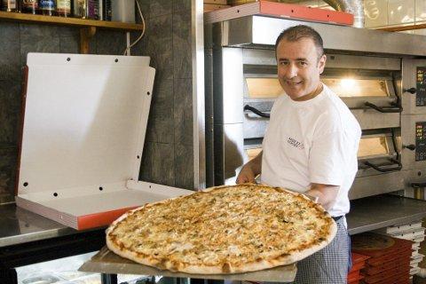 ENORM: Her viser Mohammed Hamouche frem familiepizzaen de mener er størst i Norge.
