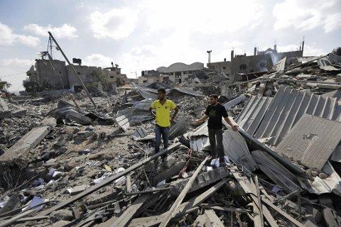 BARE RUINER: Palestineren Muhammed Abu Auda (til venstre) - her med slektningen Yousef Abu Auda - undersøker lørdag det som er igjen av farens hus etter et israelsk angrep i Beit Hanoun på Gazastripen.