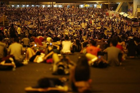 Protesters block the main street to the financial Central district outside the government headquarters in Hong Kong Protesters block the main street to the financial Central district outside the government headquarters in Hong Kong, September 29, 2014. Riot police advanced on Hong Kong democracy protesters in the early hours of Monday, firing volleys of tear gas that sent some fleeing as others erected barricades to block the security forces amid chaotic scenes in the former British colony. REUTERS/Carlos Barria (CHINA - Tags: CIVIL UNREST POLITICS)