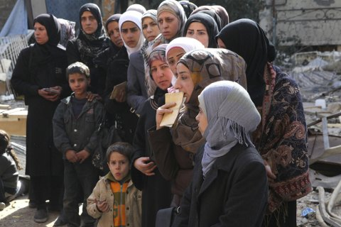 FLYKTNINGER: Velgerne er delt i hvorvidt Norge skal ta imot 10.000 syriske kvoteflyktnigner. Her syrere i Yarmok flyktningeleir som venter på å få utdelt mat.