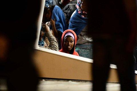 VEL I HAVN: En tredel fra Syria. Det andre og tredje mest vanlige landet er Afghanistan og Eritrea, ifølge nye rapport. Bildet viser flyktninger på vei inn til havn i Augusta på Sicilia 7. juni i år.