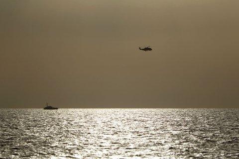 LETER: Et italiensk marinehelikopter og kystvaktskip under søk- og redningsaksjone utenfor Libya onsdag der en fiskebåt med et stort antall migranter kantret.