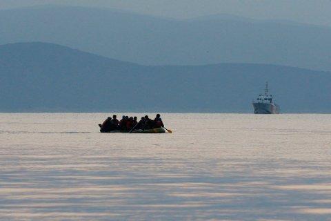ENKEL FARKOST: Migranter padler i vei på Middelhavet i en enkel farkost, her i et forsøk på å nå land på greske Kos. Bildet er tatt lørdag. I bakgrunnen, et tyrkisk kystvaktskip.