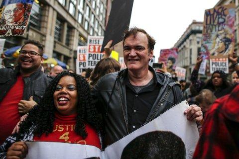 Filmregissør Quentin Tarantino deltar på en protestmarsj i New York mot politivold forrige uke. Nå sier politiet at de vil aksjonere mot ham.