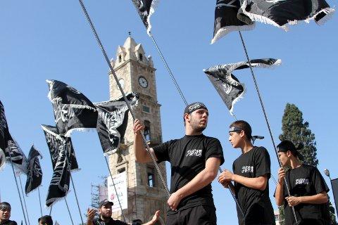 Sympatisører og medlemmer av det islamistiske partiet Hizb ut-Tahrir bærer flagg i Tripoli i Libanon i midten av oktober i år.