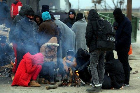 VENTER PÅ GRENSA: Flyktninger og migranter forsøker å holde varmen mens de venter på en mulighet til å krysse grensa fra Hellas over til Makedonia. Bildet er tatt nær Idomeni onsdag.