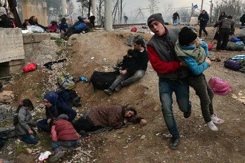 TÅREGASS: En ung gutt blir evakuert, mens andre migranter og flyktninger ligger på bakken etter tåregassangrepet fra makedonsk politi ved grensen til Hellas.