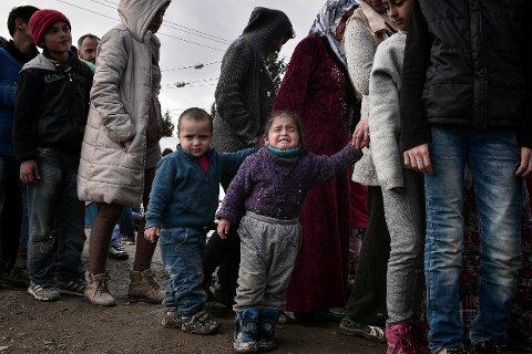 I MATKØ: Flyktninger og migranter i matkø ved den gresk-makedonske grensen nær Idomeni tirsdag.