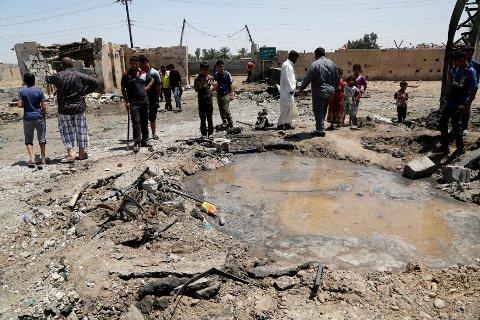 Folk samler seg rundt krateret fra et bombeangrep i en forstad sørøst i Bagdad lørdag. Over 20 mennesker ble drept.