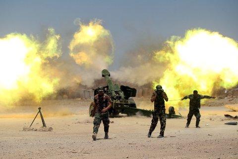 HARDE KAMPER: Irakiske styrker avfyrer sitt artilleri mot IS-stillinger nær Falluja søndag.